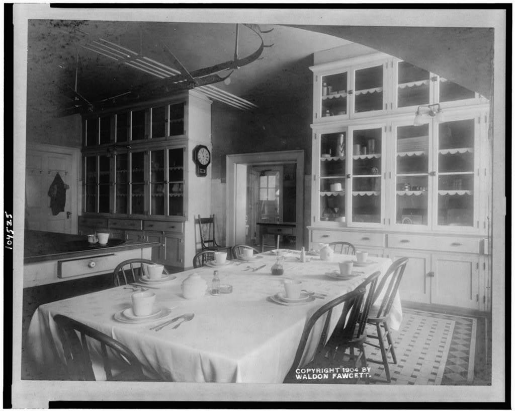 [White House kitchen with set table and cupboards]