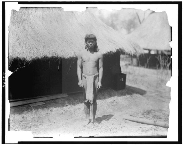 [Young man in traditional clothes beside thatch-roofed structure in Igorot village, Louisiana Purchase Exposition]