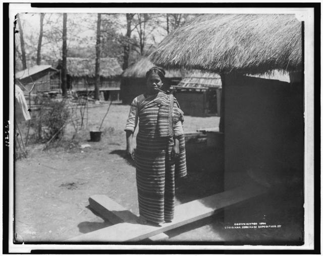 [Young woman in traditional clothing, smoking pipe, in Igorot village of Louisiana Purchase Exposition]