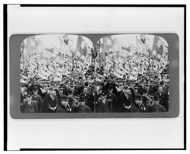 [A large crowd, mostly of men, carrying flags and banners, at a rally in Japan]