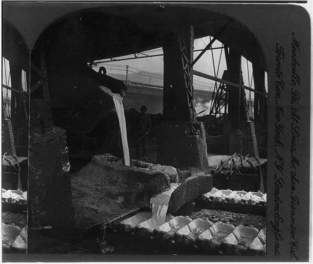A quarter front view of ladle puring [sic] off molten metal into pig iron machines, Pittsburg, Pa.