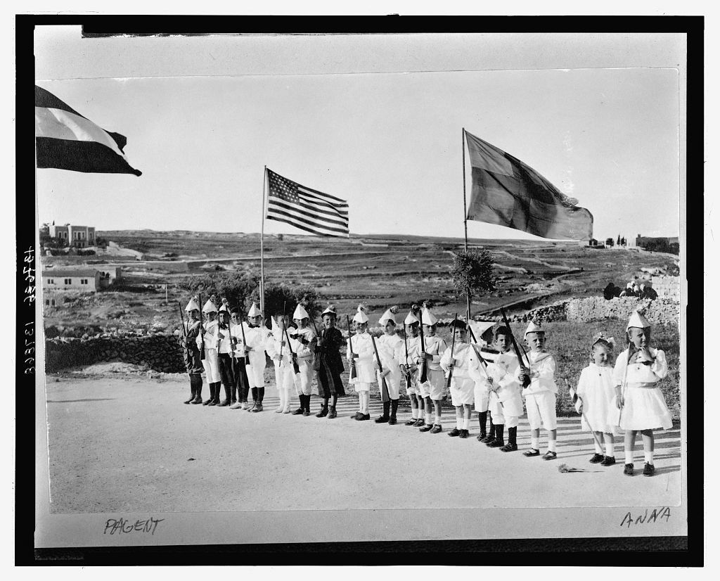 [American Colony children in Fourth of July pageant, Jerusalem, showing boys lined up holding toy rifles and Anna Grace and Tanetta Vester holding flags]