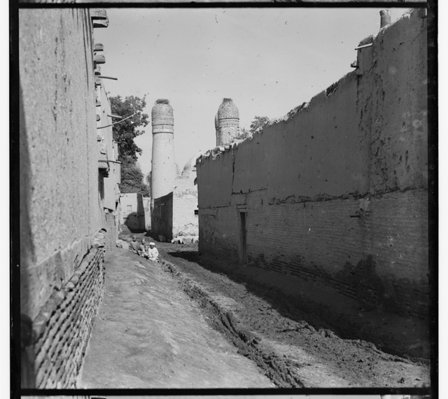 [Children sitting along passageway, two minarets topped with birds' nests in backgroud]