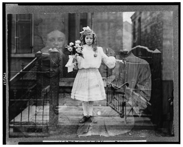 """[Double exposure """"spirit"""" photograph of girl standing, holding flowers, surrounded by spectral figures of three people] / photograph by G.S. Smallwood, Chicago, Ill."""