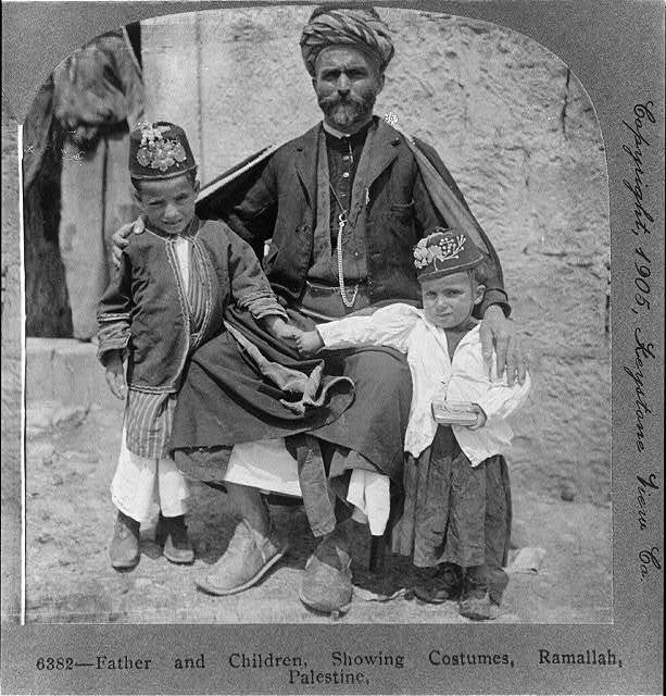 Father and [2] children, showing costumes, Ramallah, Palestine