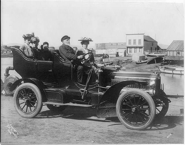 [Five persons, possibly tourists and a guide, in an automobile]