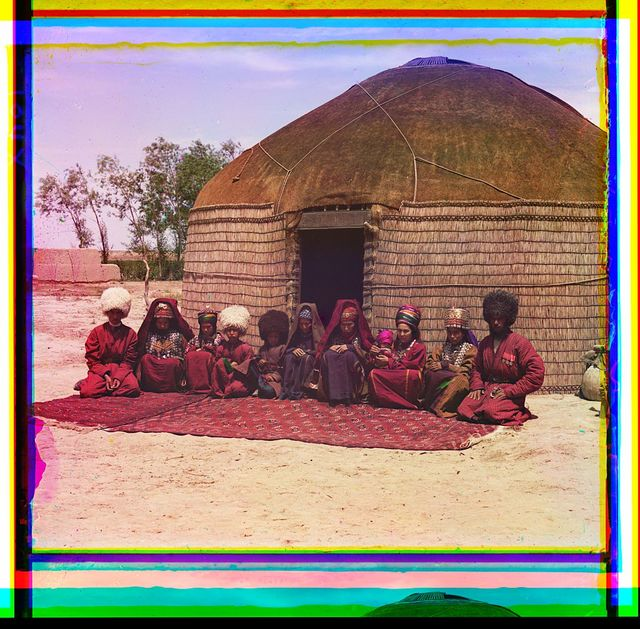 [Group of eleven adults and children, seated on a rug, in front of a yurt]