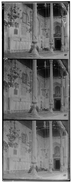 [Group of men seated on rugs, praying, under hanging candalabras, inside a mosque(?)]