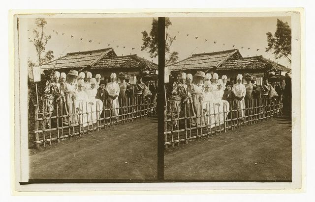 [Group portrait of Japanese medical personnel and others dressed in Western and traditional style clothing seated  near a building over which hang small flags]