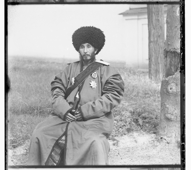 [Isfandiyar, Khan of the Russian protectorate of Khorezm(Khiva), full-length portrait, in uniform, seated on chair, outdoors]