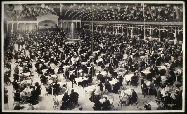 [Large banquet hall filled with people at tables, fountain in center]