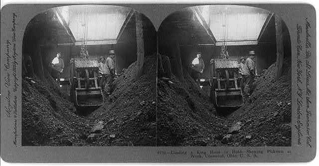 Loading a king hoist in hold [of iron ore ship] - showing pickmen at work, Conneaut, Ohio