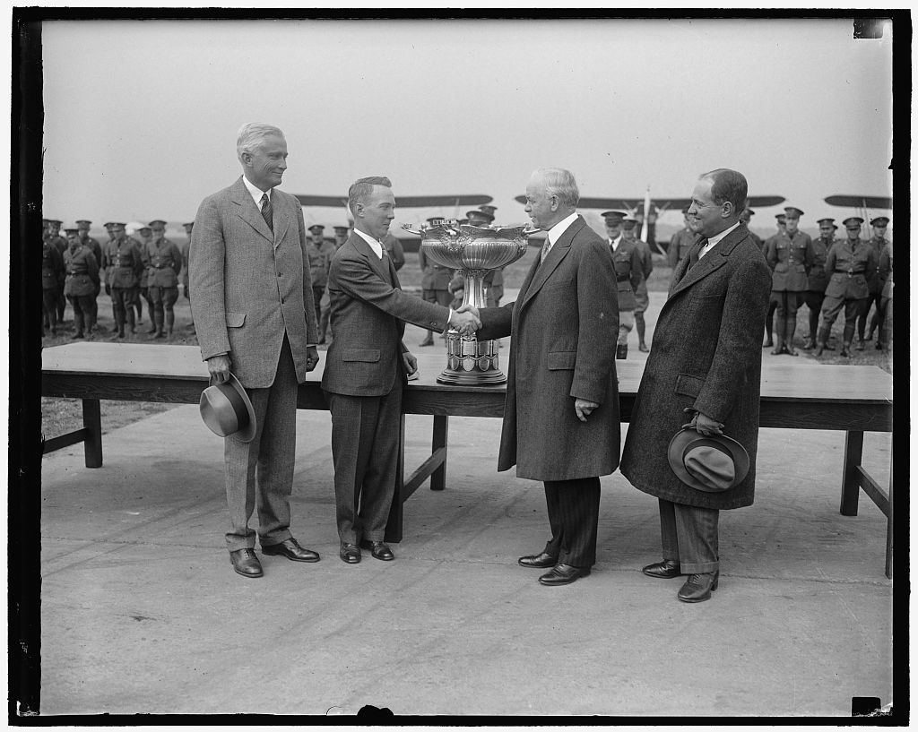 Mackay Trophy is awarded to army av[...] Secretary of War James W. Good, co [...] lating Lieut. Harry A. Sutton, Army [...] aviator, after presenting him the Mackay Trophy for 1928 at Bolling Field, Wash[...] Lieut. Sutton received the trophy for [...] performing the most meritorious flight [...] Army pilots during 1928. He volunta[...] engaged in dangerous flight tests in [...] he determined the spinning character[...] of several types of observation and [...] planes. Others in the picture [...] Senator Hiram Bingham (left) of Conn. [...]