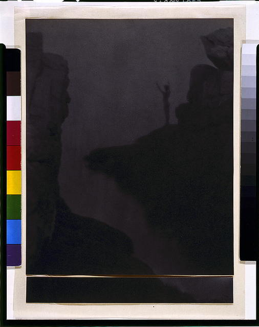 [Nude boy in rocky landcape above water, arms raised, silhouette] / FHD 1905.