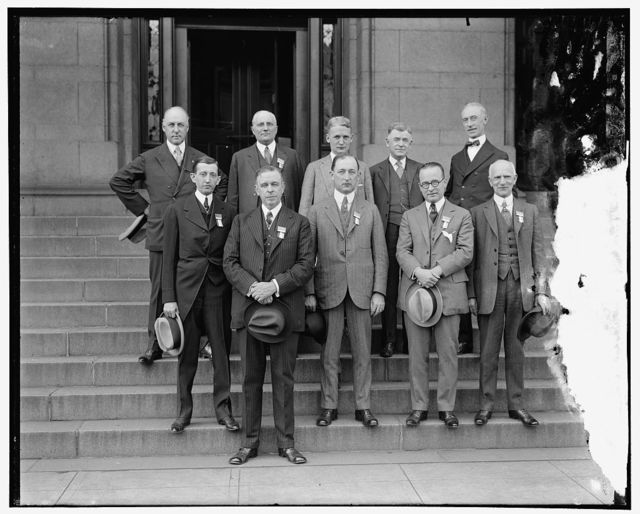 Postmaster General Will Hays with his four assistants. L to R, [Unidentified, First Assistant Postmaster General Hubert Work]; Second Assistant Postmaster General E.H. Shaugnnessy; Third Assistant Postmaster General W. Irving Glover; Fourth Assistant Postmaster General Harry H. Hillany. Back row: W. Mooney; Rush D. Simmons; G.W. Perkins; T.L. Degman; John H. Edwards