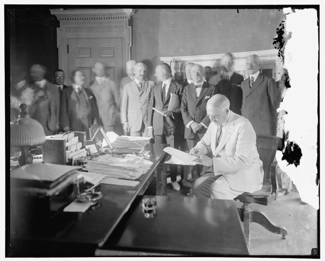 Pres. Harding signing the Edge-Ansorge Resolution for the development of the New York Port along lines proposed by the joint commission of N.Y. and N.J. in the treaty entered into by the two states on April 30, 1921. The treaty looks to general relief from congestion the harbor and was endorsed by the War Department. Rep. Martin C. Ansorge, or New York, sponsor of the resolution is standing (third) from President Harding, with papers under arm