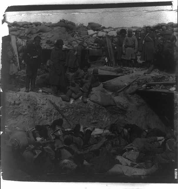 [Russian soldiers looking down at a trench filled with corpses of Japanese soldiers, Port Arthur]
