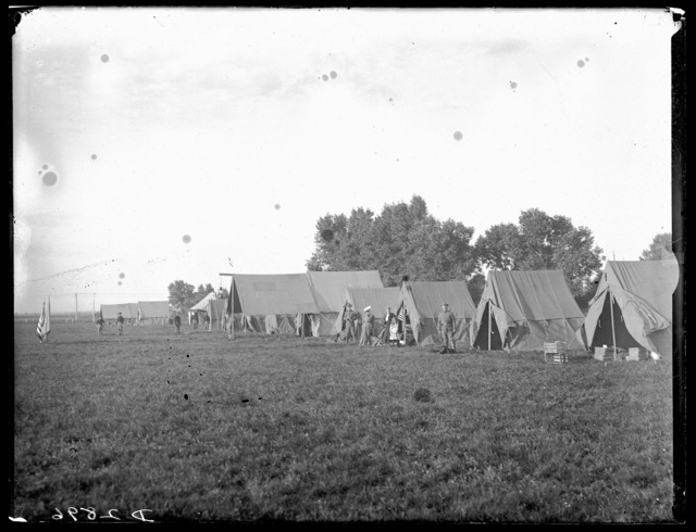 Several soldiers, two woman, and a small girl standing outside tents at the Nebraska National Guard Camp, Kearney, Nebraska