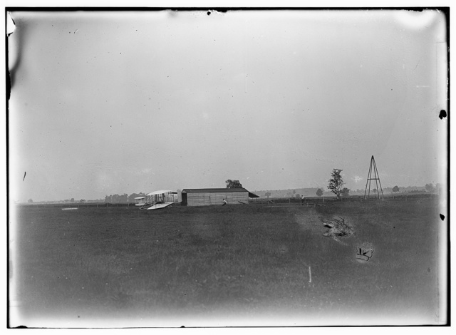 [Start of the first flight of 1905, Orville Wright at controls of the machine, near the hangar at Huffman Prairie. The two figures in the center are probably Wilbur Wright and Charles E. Taylor. The catapult launching device appears for the first time in a photograph]
