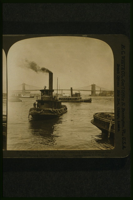 The busy harbor of New York - showing Brooklyn Bridge and Williamsburg Bridge in distance