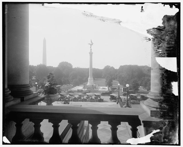 The impressive World War Memorial, the First Division Monument, erected just south of the State War and Navy Building, Washington. It will be dedicated on October 4th. It is a granite shaft with a gold figure at the top. The Washington Monument is shown in background