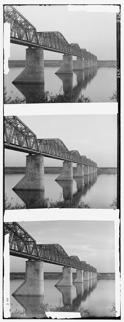 [Trans-Siberian Railway metal truss bridge on stone piers, over the Kama River near Perm, Ural Mountains Region]