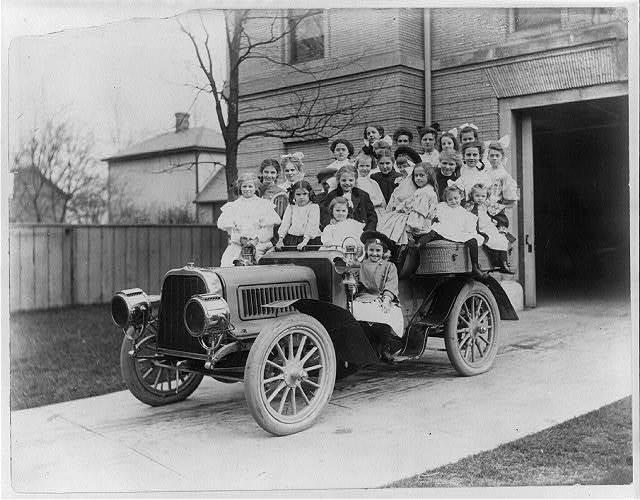 [Twenty-four little girls posed in an automobile]