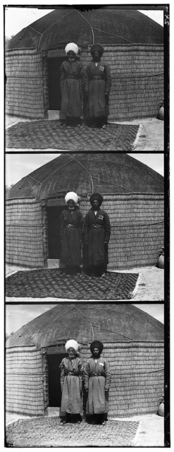 [Two men standing on a rug, in front of yurt]