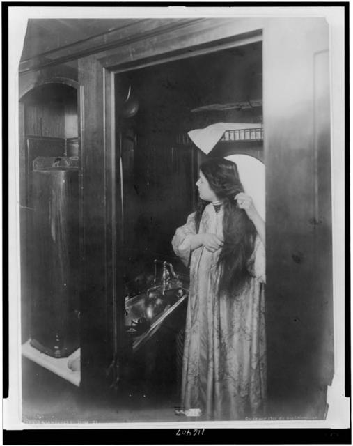 [Woman combing her hair in ladies' toilet room, tourist sleeper, in railroad car]