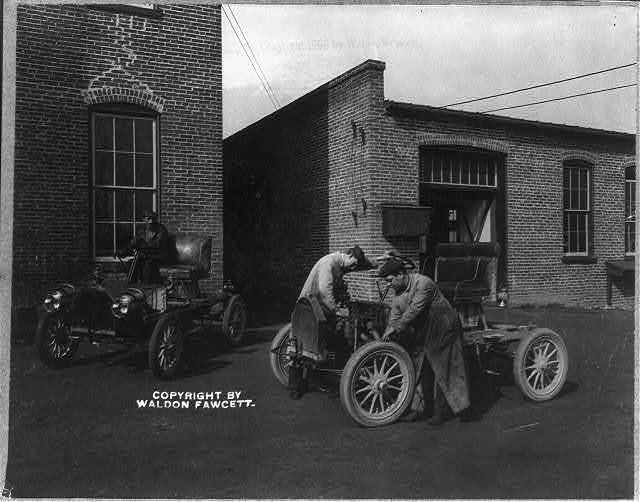 [2 men working on an automobile outside of automobile plant]