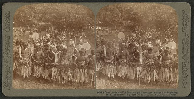 A feast day in the Fiji Islands -- gaily bedecked natives just beginning the national dance