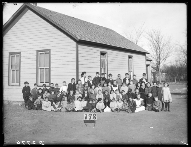 A group of students and their teacher, Miss Emma Dellveg, in front of the Arcadia School, Arcadia, Nebraska.