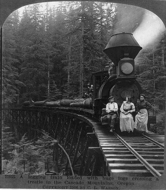 A logging train loaded with huge logs crossing a trestle in the Cascade Mountains, Ore.