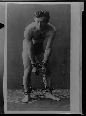 [Houdini, full-length portrait, standing, facing front, in chains]