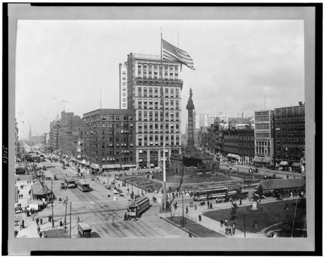 [Public square showing monument, department stores, banks, trolley cars, pedestrians in Cleveland, Ohio]