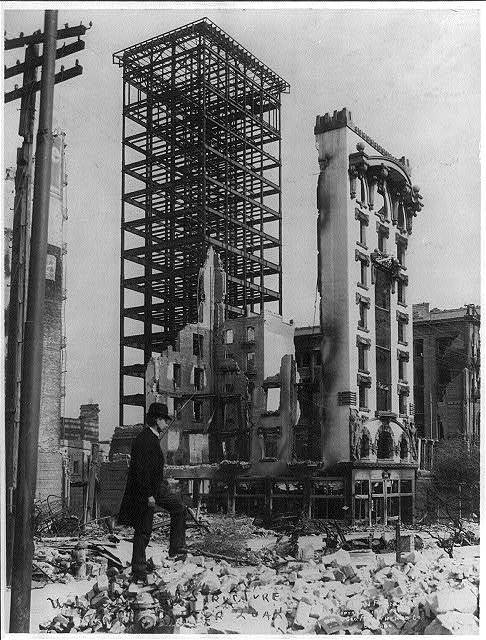 San Francisco disaster - earthquake and fire - man standing among rubble in foreground and unfinished steel structure of building and facade of another still intact in background
