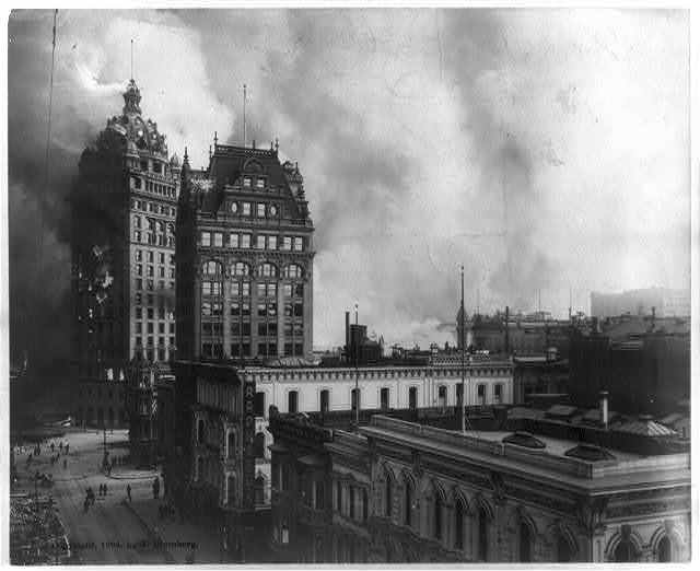 San Francisco disaster - earthquake and fire - several buildings in foreground, one large building on fire, other buildings and smoke in background
