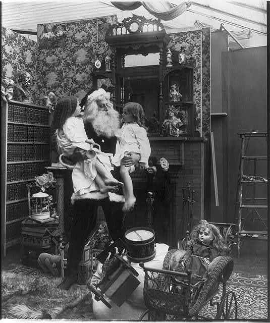 [Santa Claus with children and toys: Santa holding 2 girls]