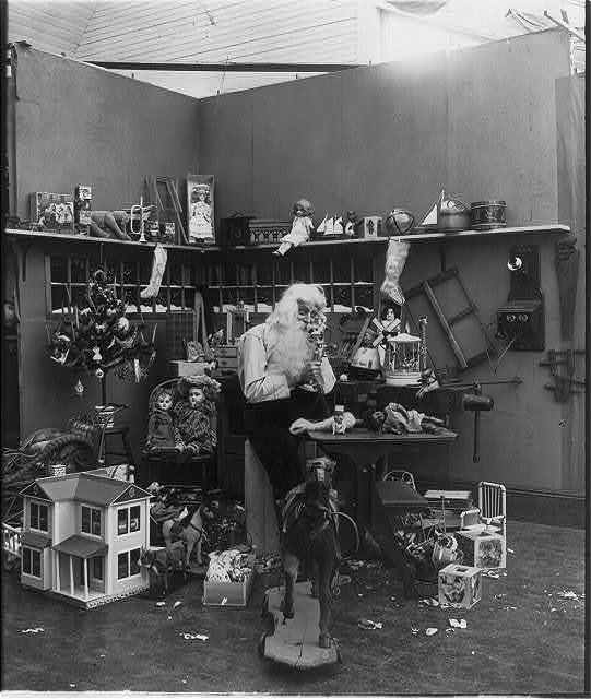 [Santa Claus with children and toys: Santa in his workshop talking on telephone and surrounded by toys]