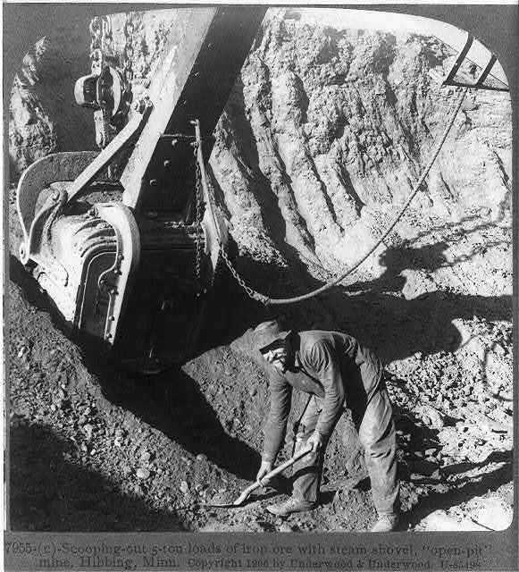 """Scooping-out 5-ton loads of iron ore with steam shovel,  """"open-pit"""" mine, Hibbing, Minn."""