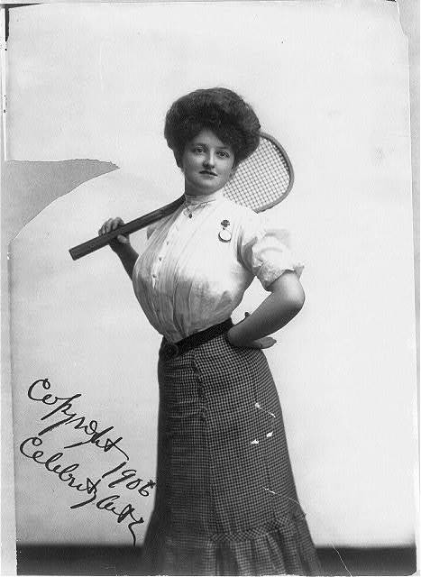 """[""""Tennis Girl"""" - woman posed with tennis racket on shoulder, three-quarters length, standing, facing front]"""