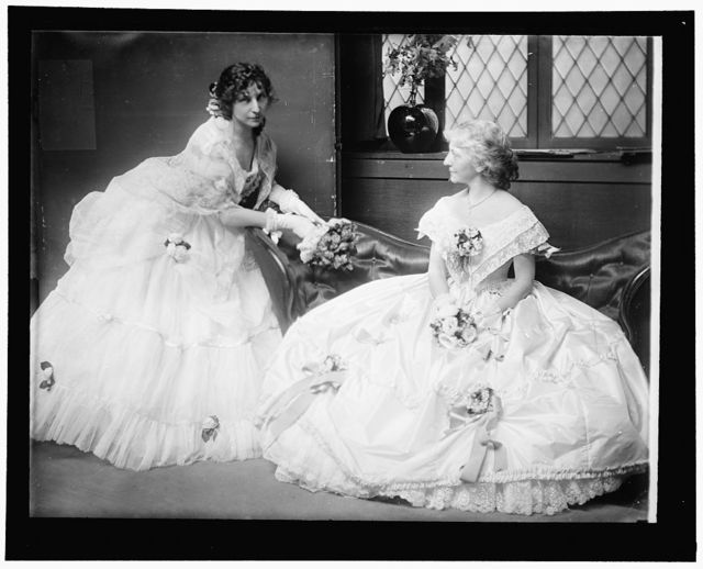 [The Gerson sisters posed on a sofa in their Crinoline Ball costumes. New York City]