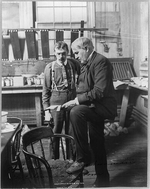 [Thomas Alva Edison, 1847-1931, full-length portrait, standing, facing left, with his workman in the chemical room]
