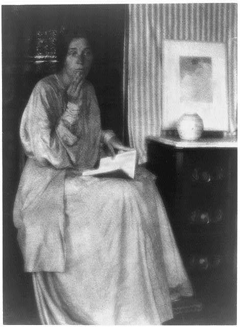 [Woman (Beatrice Baxter Ruyl), in dress with open book in lap and hands to face, seated]