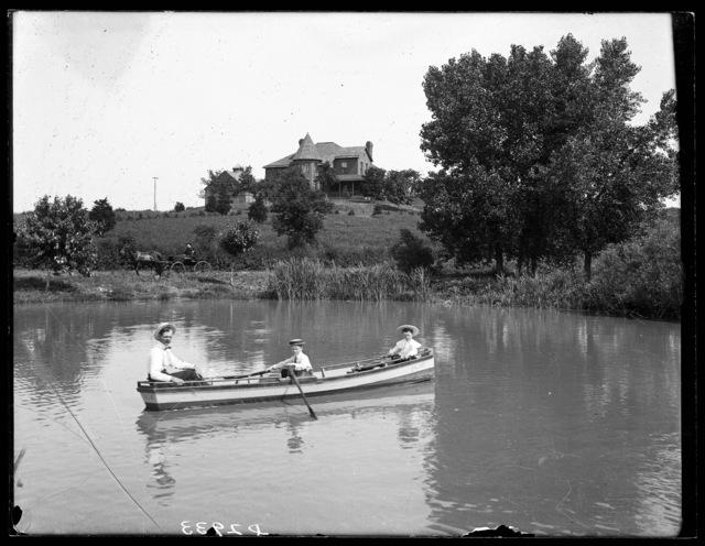 C.B. Reynolds and two small children in boat on a lake near the Reynolds residence near Kearney, Nebraska.