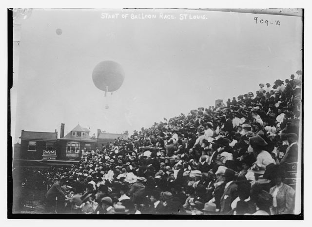 Crowd in stands, balloon overhead, at start of balloon race, St. Louis