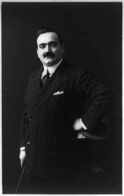 [Enrico Caruso, 1873-1921, three-quarters length portrait, standing, facing left]