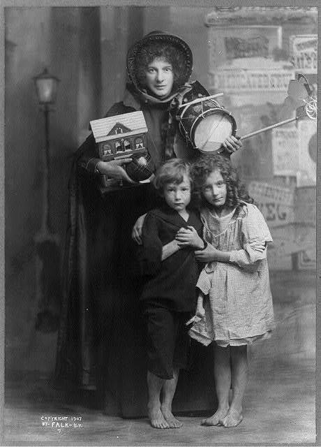 """[Evangeline Cory Booth, 1865-1950, full length, standing, holding several toys, facing slightly left, girl with arm around boy in front of her; posed """"poverty"""" photo for Salvation Army?]"""
