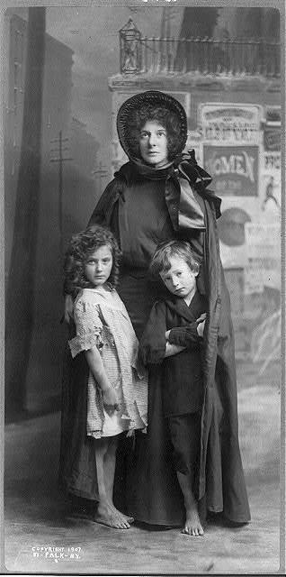 [Evangeline Cory Booth, 1865-1950, standing, in Salvation Army dress, facing front; with 2 children]