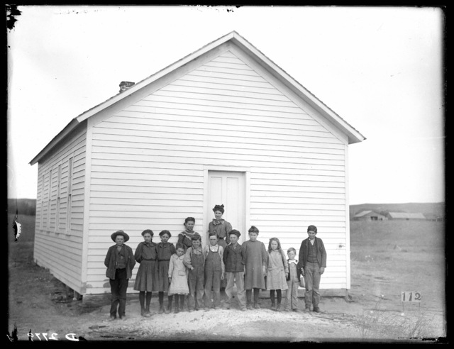 Group of students and teacher in front of a school, Buffalo County, Nebraska.
